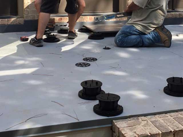tiles being laid on deck using pedestals over in Duradek's Plazadek System