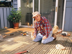 Homeowner laboring on refinishing wood deck