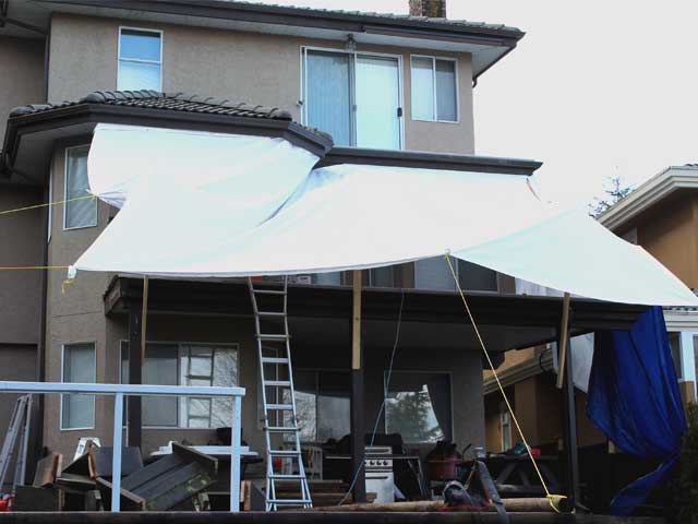 Deck under tarp for installation of Duradek vinyl in the rain.